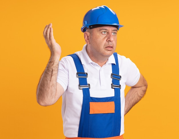 Nieświadomy budowniczy dorosły kaukaski mężczyzna w mundurze stoi z podniesioną ręką i patrzy z boku na pomarańczowy