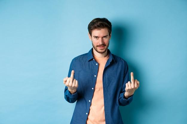 Nieświadomy i niezadowolony mężczyzna pokazujący środkowe palce i niechętnie patrząc w kamerę, nie daje się pieprzyć, stojąc na niebieskim tle.