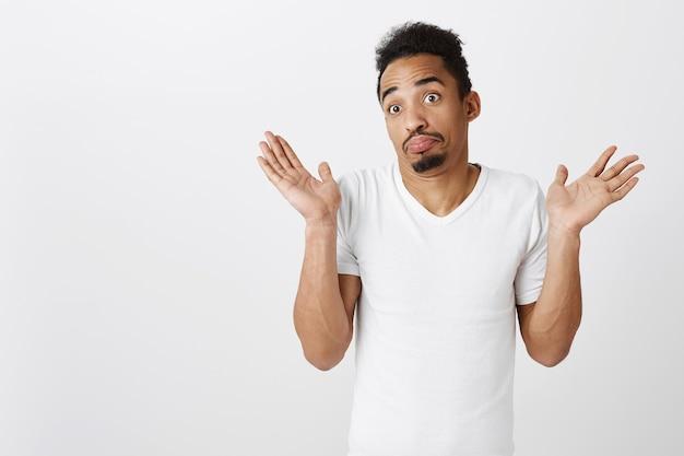 Nieświadomy i zdezorientowany afroamerykanin wzrusza ramionami nieświadomy, nic nie wie