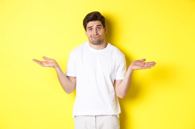 Nieświadomy mężczyzna w białej koszulce, wzruszający ramionami i zdziwiony, nic nie wiem, stojący nad żółtą ścianą