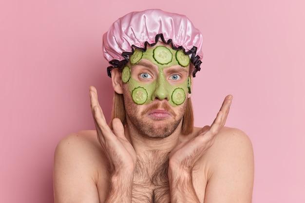 Nieświadomy mężczyzna z zarostem i wąsami unosi dłonie nad twarzą z wahaniem nakłada zieloną maskę kosmetyczną z kawałkami ogórka stoi z odkrytymi ramionami i nosi kapelusz kąpielowy.