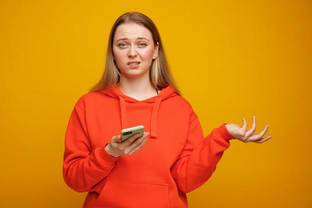 Nieświadomy młoda blondynka trzyma telefon komórkowy pokazuje pustą rękę