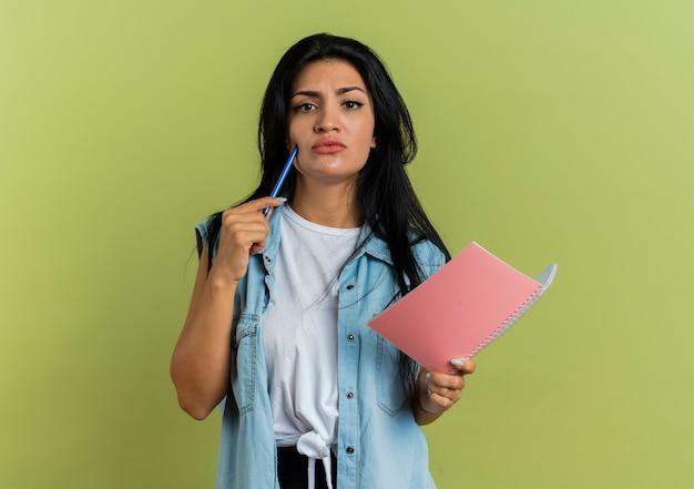 Nieświadomy młoda dziewczyna kaukaski stawia pióro na brodzie i trzyma notes na białym tle oliwkowej zieleni z miejsca na kopię
