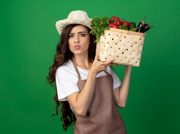 Nieświadomy młoda kobieta ogrodniczka w mundurze na sobie kapelusz ogrodniczy trzyma kosz warzyw na zielonej ścianie z miejsca na kopię