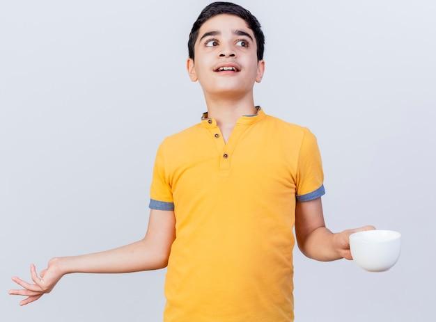 Nieświadomy młody chłopiec kaukaski, patrząc na bok, pokazując pustą dłoń trzymającą kubek na białym tle