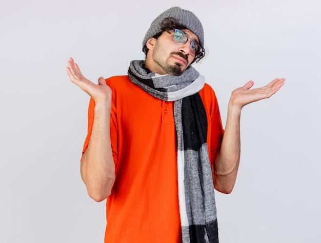 Nieświadomy młody chory człowiek w okularach czapka zimowa i szalik patrząc z przodu pokazując puste ręce na białej ścianie