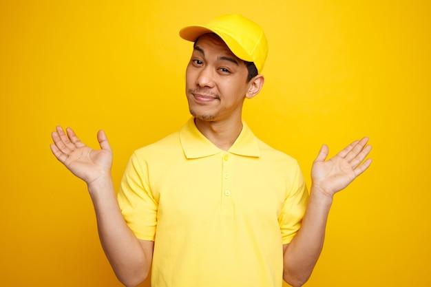Nieświadomy młody doręczyciel w czapce i mundurze pokazuje puste ręce