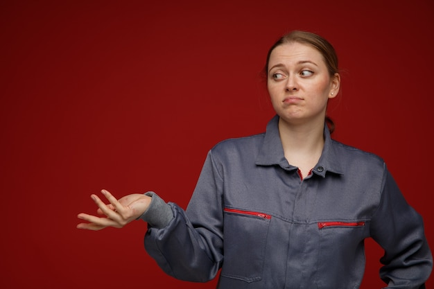 Nieświadomy młody inżynier blond kobieta ubrana w mundur, patrząc na bok, pokazując pustą rękę