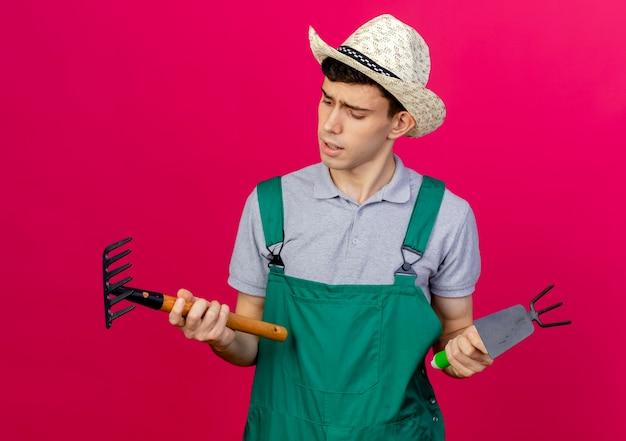 Nieświadomy młody męski ogrodnik w kapeluszu ogrodniczym trzyma grabie motyka i patrzy na grabie