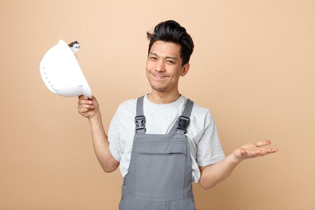 Nieświadomy młody pracownik budowlany w mundurze trzymając kask pokazujący pustą rękę