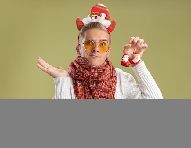 Nieświadomy młody przystojny facet w opasce świętego mikołaja i szaliku trzymającym świąteczne ozdoby świętego mikołaja pokazujące pustą rękę odizolowaną na oliwkowej ścianie