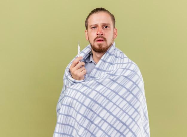 Nieświadomy młody przystojny słowiański chory mężczyzna owinięty w kratę trzymający termometr patrząc na kamerę odizolowaną na oliwkowozielonym tle z kopią miejsca