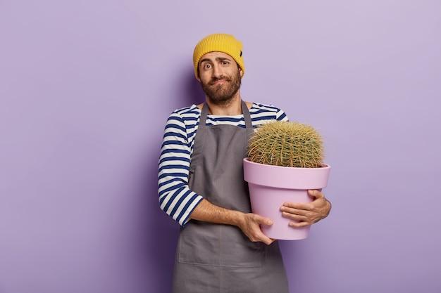 Nieświadomy sprzedawca pozuje w kwiaciarni z doniczką z kaktusem