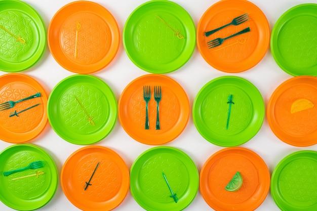 Niesystematyczna konsumpcja. jednorazowe przybory plastikowe leżące na jasnych talerzach jako instalacja do kampanii antyplastycznej