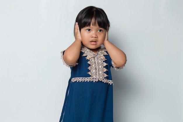 Nieszczęśliwa azjatycka dziewczynka zamyka uszy na białym tle