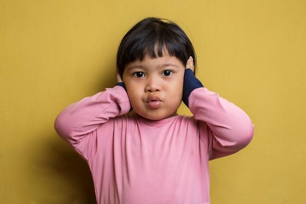 Nieszczęśliwa azjatycka dziewczynka zamyka uszy