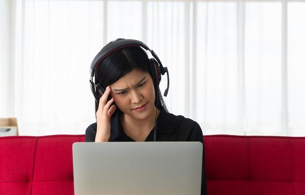 Nieszczęśliwa azjatycka kobieta siedzi na kanapie i wideokonferencja z partnerem biznesowym na laptopie