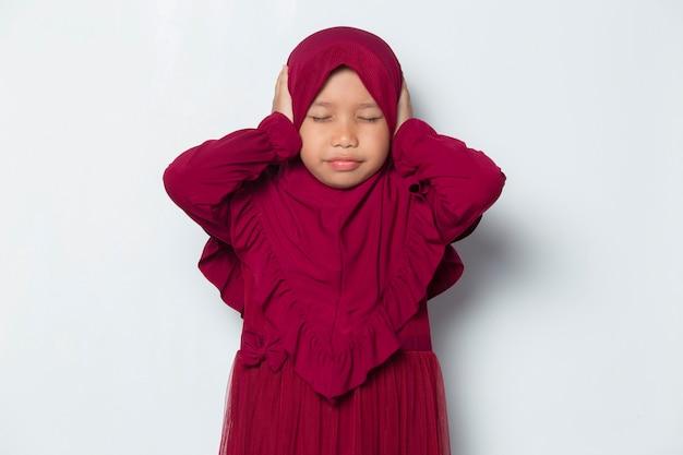 Nieszczęśliwa azjatycka muzułmańska dziewczynka zamyka uszy na białym tle