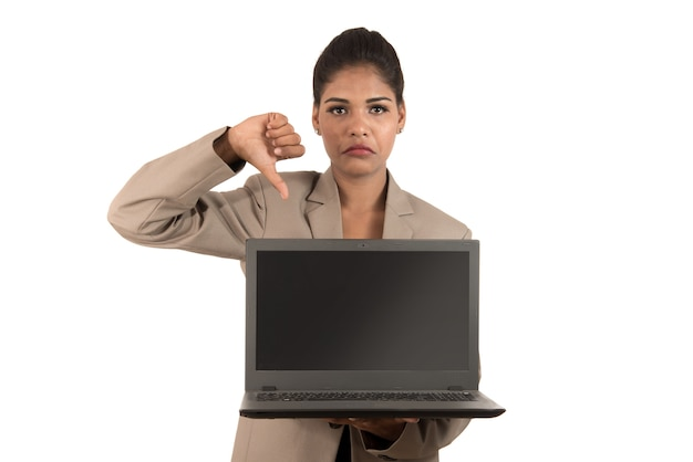 Nieszczęśliwa biznesowa kobieta trzyma laptop i pokazuje kciuki w dół na białym tle