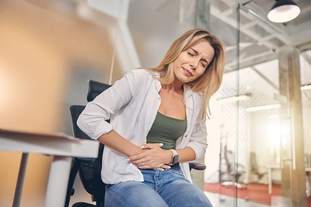 Nieszczęśliwa blondynka czuje ból w brzuchu siedząc na krześle w pracy