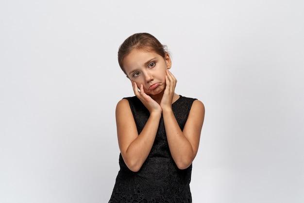 Nieszczęśliwa dziewczyna patrzy w kamerę, z urazą wystawia wargę, unosząc ręce do góry. dziewczyna naprawdę chciała psa lub czworonożnego przyjaciela, a jej rodzice oszukiwali.