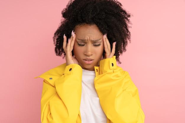 Nieszczęśliwa kobieta afro w żółtym płaszczu przeciwdeszczowym cierpi na silny pulsujący ból głowy dotykający jej skroni