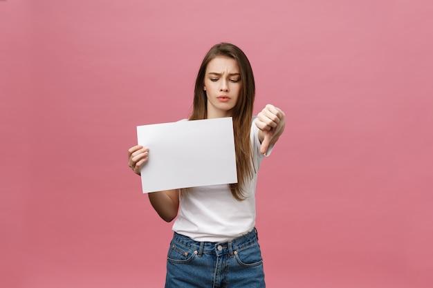 Nieszczęśliwa kobieta daje kciuki w dół gestowi z pustym papierem