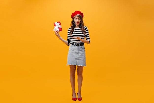 Nieszczęśliwa kobieta na dżinsowej spódnicy i pasiastej koszuli trzyma pudełko. smutna dziewczyna w nowoczesne ubrania pozowanie na na białym tle.