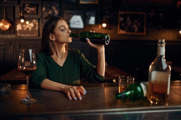 Nieszczęśliwa kobieta pije alkohol przy kasie w barze