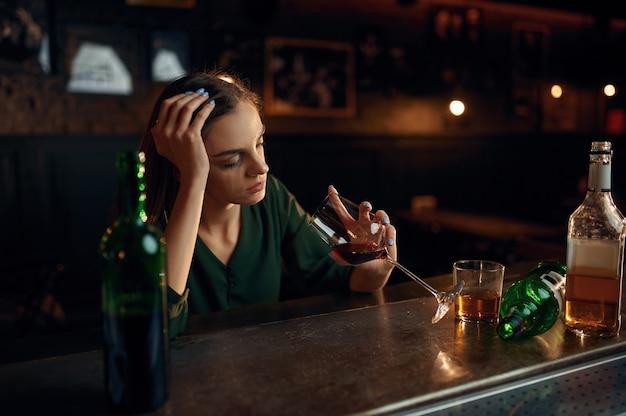 Nieszczęśliwa kobieta pije napój alkoholowy przy kasie w barze