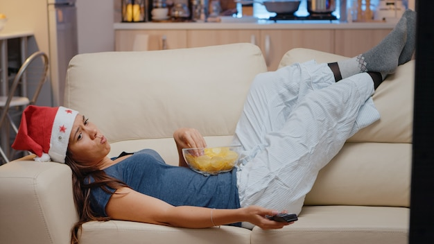 Nieszczęśliwa kobieta samotnie oglądająca telewizję w wigilię bożego narodzenia