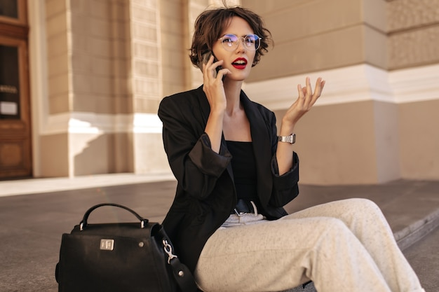 Nieszczęśliwa kobieta w czarnej kurtce i okularach rozmawia przez telefon na zewnątrz. nowoczesna kobieta z czerwonymi ustami i kręconymi włosami siedzi na zewnątrz.