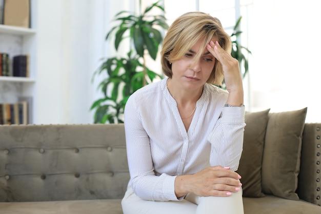 Nieszczęśliwa kobieta w średnim wieku siedzi na kanapie w salonie.