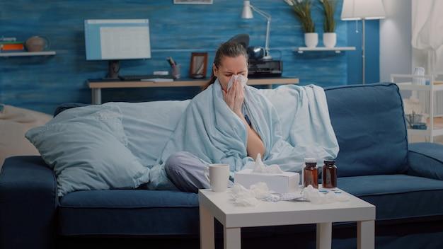 Nieszczęśliwa kobieta z grypą używa chusteczek do wydmuchania kataru