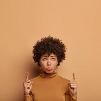 Nieszczęśliwa kobieta z kręconymi włosami czegoś nie lubi, wskazuje powyżej, zaciska dolną wargę, ma ponury wyraz twarzy, nosi poloneck