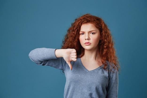 Nieszczęśliwa ładna kobieta z czerwonymi kręconymi włosami i piegami o smutnym i zmęczonym wyrazie twarzy, pokazująca kciuk w dół.