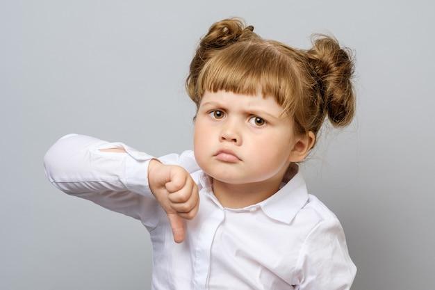 Nieszczęśliwa mała dziewczynka pokazuje kciuka puszek