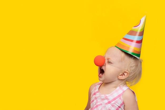 Nieszczęśliwa mała dziewczynka w świątecznym kapeluszu i błazen nosie na kolorze żółtym