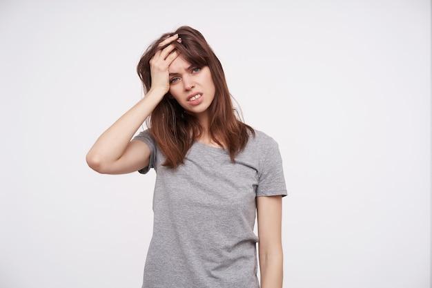 Nieszczęśliwa młoda atrakcyjna dama z przypadkową fryzurą, trzymając dłoń na głowie, patrząc ze zmęczeniem na aparat i marszcząc brwi, odizolowane na białym tle
