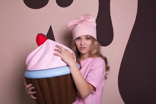Nieszczęśliwa młoda blondynka w różowej koszulce i czapce bawi się dużą babeczką