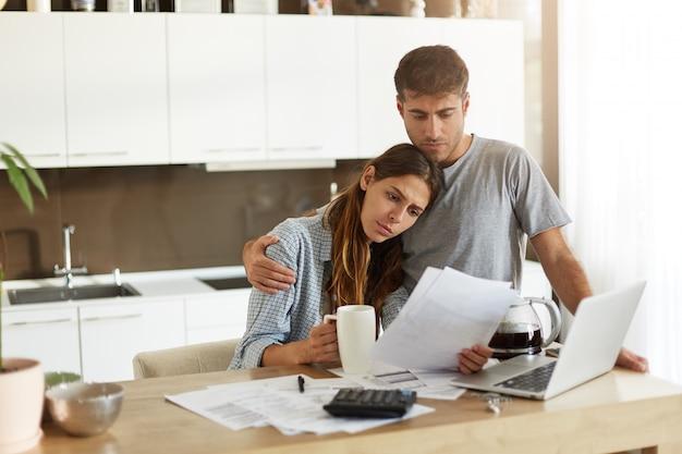 Nieszczęśliwa młoda europejska rodzina w obliczu kłopotów finansowych: smutny mąż pogrążony w myślach przytulający zmartwioną żonę, która studiuje powiadomienia z banku, podczas robienia finansów w kuchni