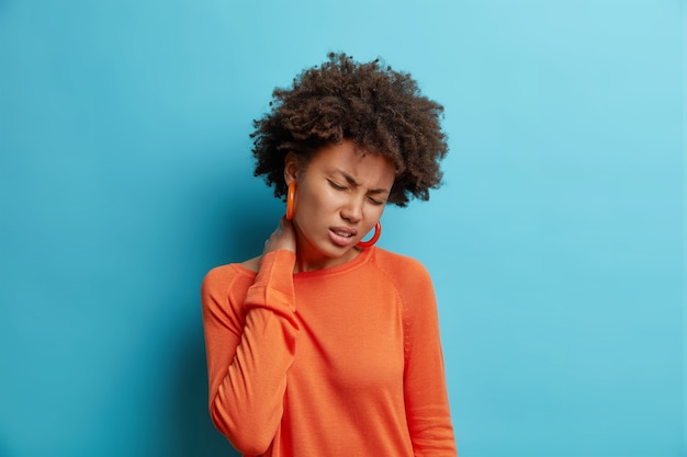 Nieszczęśliwa młoda kobieta cierpi na ból szyi czuje zmęczenie masaże szyja odczuwa dyskomfort zamyka oczy nosi swobodny pomarańczowy sweter odizolowany na niebieskiej ścianie