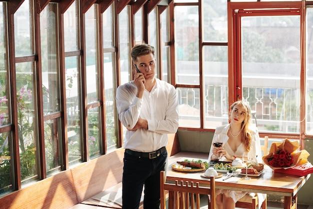 Nieszczęśliwa młoda kobieta, patrząc na chłopaka, rozmawia przez telefon ze współpracownikiem podczas romantycznej randki