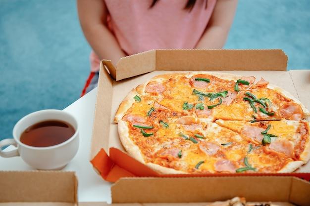 Nieszczęśliwa młoda kobieta patrząc na pizzę w pudełku po pizzy. dieta dla dorosłych i rezygnacja z glutenu, mąki pszennej i koncepcji piekarni. łamanie zasad diety, rezygnacja z diety. dieta bezglutenowa i kontrola otyłości.