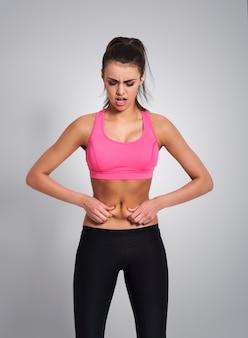 Nieszczęśliwa młoda kobieta szczypanie brzucha
