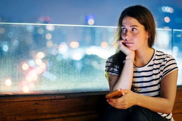Nieszczęśliwa młoda kobieta trzyma smartphone w wieczór pejzażu miejskim