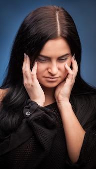 Nieszczęśliwa młoda kobieta ze złym bólem głowy