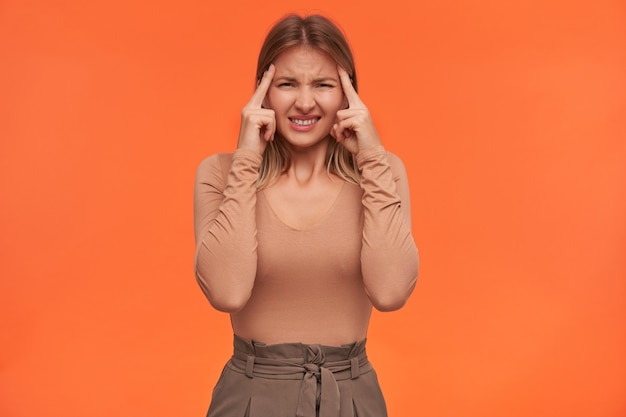 Nieszczęśliwa młoda ładna białogłowa kobieta z krótką fryzurą marszczącą brwi, mając silny ból głowy i unoszącą ręce do skroni, pozując nad pomarańczową ścianą