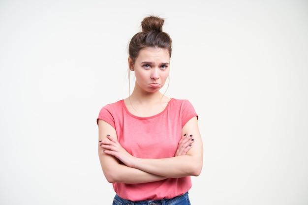 Nieszczęśliwa młoda ładna brunetka kobieta z fryzurą kok, trzymając ręce skrzyżowane na piersi, patrząc z niechęcią na kamerę, będąc odizolowaną na białym tle