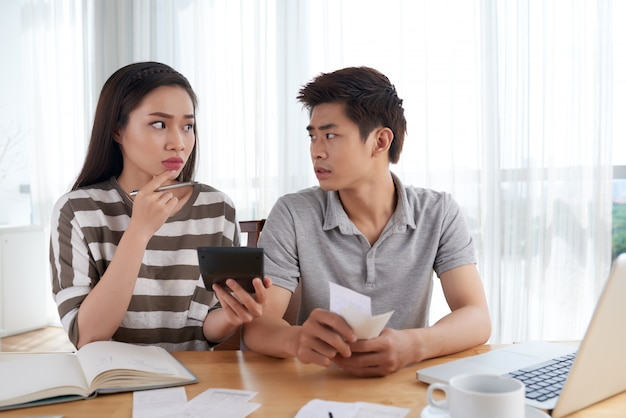 Nieszczęśliwa młoda rodzina obliczająca koszty bankrutuje